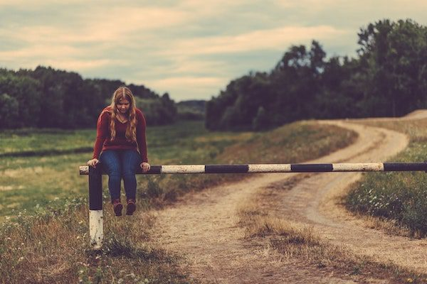 blond teen girl sitting on dirt road barrier