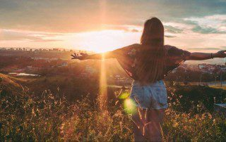 girl with arms spread looking at sunset
